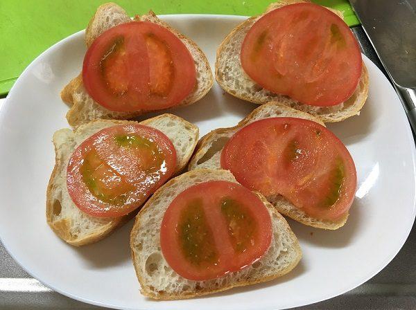 フランスパンのガーリックを塗り、トマトを載せた所